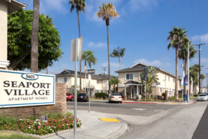 Seaport Village exterior with driveway entrance and palm trees. 5601 entrance sign