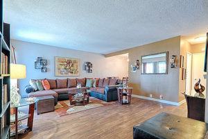 hardwood floor living room with couch, rug, decorations on wall, facing doorway