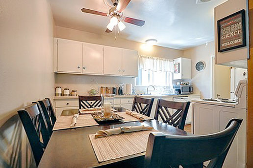 bright kitchen with white cabinets, white appliances, and brown table and chairs