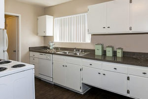 kitchen with white cabinets, granite countertops, window, white appliances