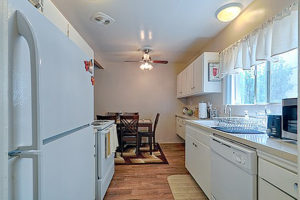 kitchen with white cabinets, light countertops, window, white appliances