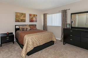carpeted bedroom with neutral tones, with queen size bed, black side table, large window and black dresser with mirror