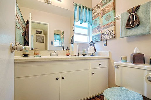 bathroom with white cabinets, mirror, blue accent decor