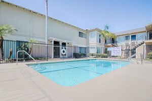 Long Beach Apartments - Seaport Village Swimming Pool Surrounded by Lounge Chairs and Gated for Safety