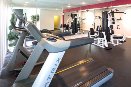Fitness center with various machines and mirrors